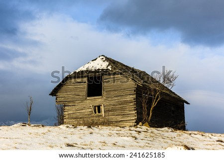 Old wooden barn in the countryside, in the winter