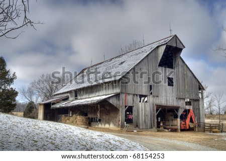 Old wooden barn on a farm in winter - stock photo