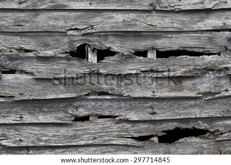 Old wooden barn wall pattern, with holes in rotten wood - stock photo