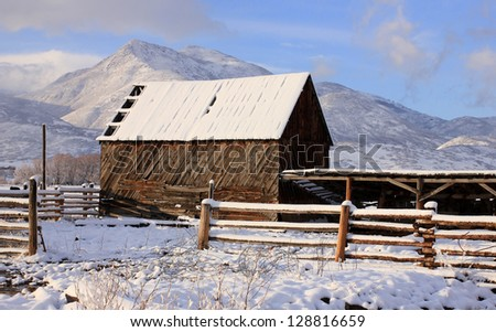 Old wooden barn with fresh snow in the rural Utah, USA. - stock photo