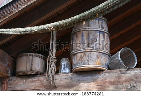 Old wooden barrel and bucket underneath the roof