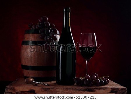 Old wooden barrel with red wine, bottle with vine