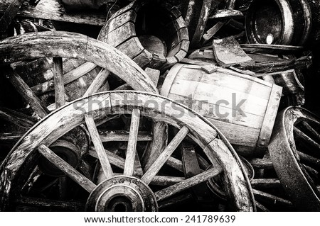 Old wooden barrels and broken wheels in retro setting - stock photo