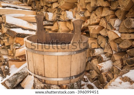 Old wooden bath bucket in the woodpile - stock photo