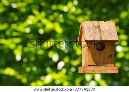 Old wooden birdhouse hanging with ropes. On a green blurred background - stock photo
