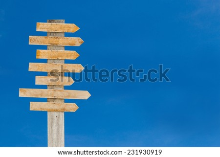 Old wooden blank sign post against the sky - stock photo