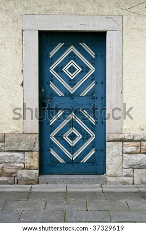 Old wooden blue door with ornament in stone wall
