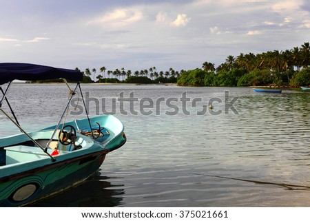 old wooden boat in bright blue water of Maldives