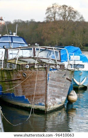 old wooden boat moored using old rope it has worn, chipped and peeling blue paint on the hull and is in need of some loving restoration by an enthusiastic sailor - stock photo