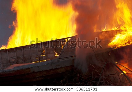 Old wooden boat on fire with high flames