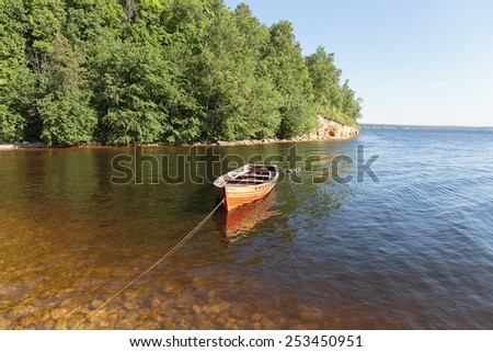 Old wooden boat on the river - stock photo