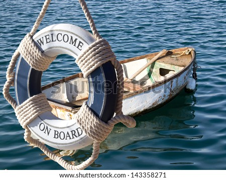 old wooden boat on the sea and safe belt with sign welcome on board - stock photo