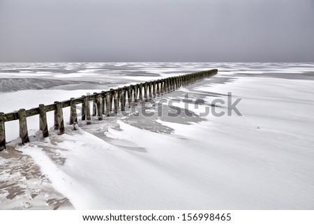 old wooden breakwater on frozen Ijsselmeer in winter, Netherlands - stock photo
