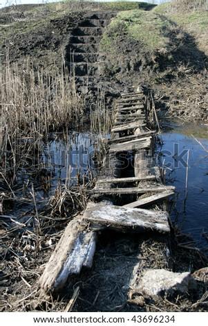 Old wooden bridge across the river - stock photo