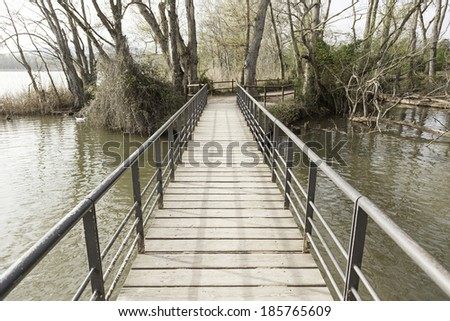 Old wooden bridge in a lake, detail of an old footbridge - stock photo