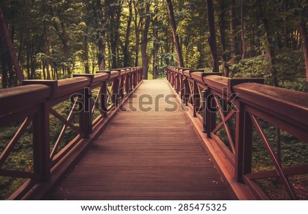 old wooden bridge in  deep forest, natural vintage background - stock photo