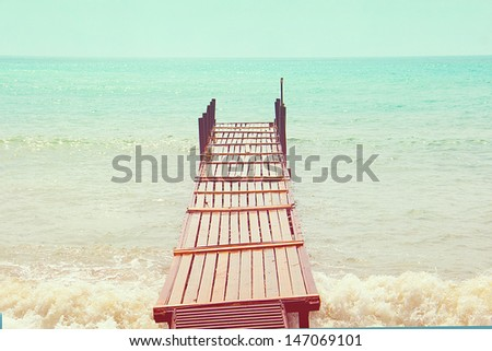 old wooden bridge in the sea in a retro style - stock photo