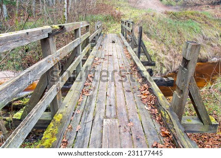 old wooden bridge over small river. autumn. - stock photo