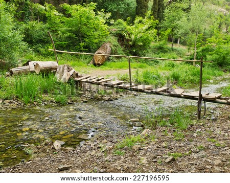 old wooden bridge over the river - stock photo