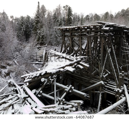 Old wooden bridge over the river in coniferous forest after first snow fall. - stock photo