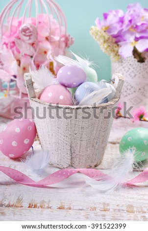 old wooden bucket with pastel color easter eggs and feathers