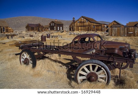 Old wooden building in ghost town and car remains - stock photo