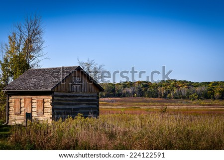 Old Wooden Cabin sitting in the field with blue sky - stock photo