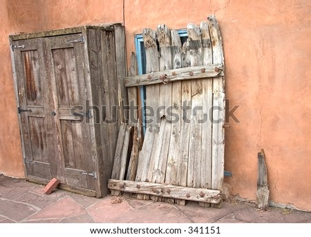Old wooden cabinet and door against a wall in a courtyard in Santa Fe, NM. - stock photo