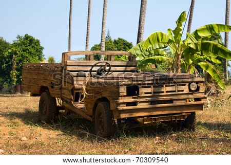 Old wooden car in the jungle . Thailand .