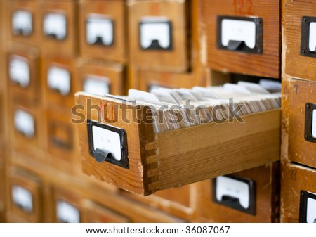 Old wooden card catalog with one opened drawer - stock photo
