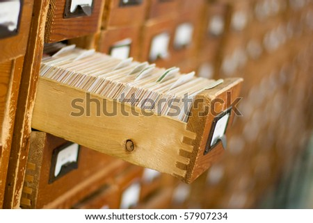 Old wooden card catalogue with one opened drawer - stock photo