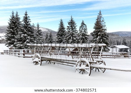 old wooden carriage in snow on winter meadow - stock photo