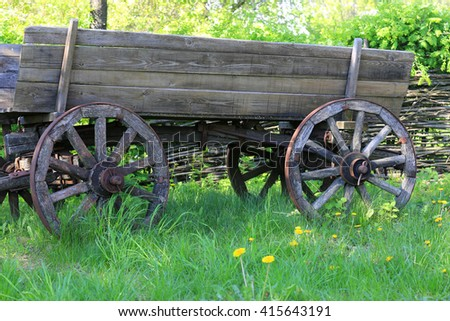 Old wooden carriage on green grass in garden
