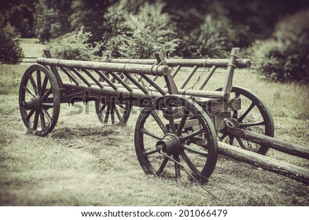 old wooden cart on field, vintage stylized photo