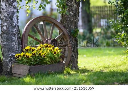Old wooden cart wheel decoration for the garden - stock photo
