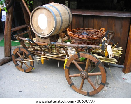 Old wooden cart with wooden barrel and grapes basket - stock photo