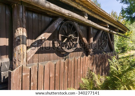Old wooden cartwheels with metal rims hanging on the wall of the wooden house - nobody  - stock photo