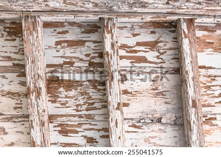 Old wooden ceiling with exposed beams and peeling paint. - stock photo