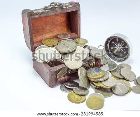 Old wooden chest with coins and white compass - stock photo