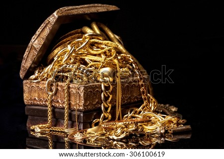 Old wooden chest with pile of various golden jewelry, isolated against black background. - stock photo