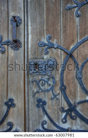 Old wooden church door with metal lock, handle and gothic style decoration