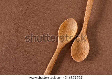 Old wooden cooking spoon on brown background - stock photo