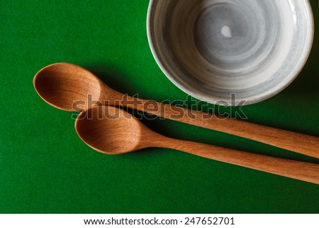 old wooden cooking spoon on green background with china cup - stock photo