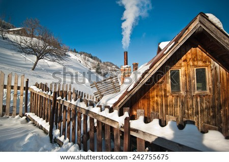 Old wooden cottage with hill covered by snow in background. Bright cold winter day in the mountains landscape. Carpathian mountains, Romania. Isolated wood mountain house cabin hut covered by snow - stock photo