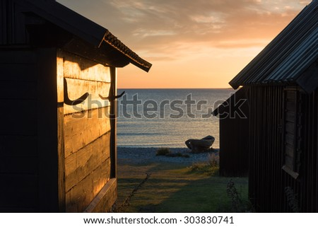 Old wooden cottages of the fishing settlement Helgumannen on the island Faroe, Sweden, in the Baltic Sea at dawn. Beautiful golden light is shimmering on the wooden planks. - stock photo