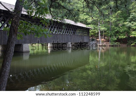 Old wooden covered bridge crossing water with green trees and bushes on the other side. - stock photo