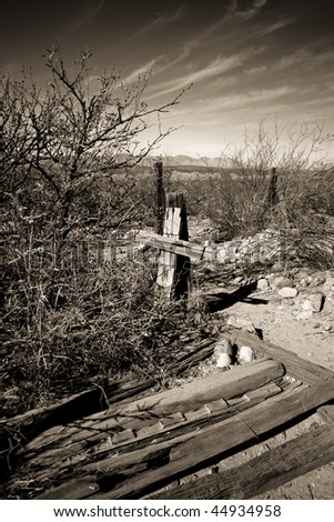 Old wooden cross and fence from Arizona ghost town graveyard with a sepia tone clouded sky and rocks - stock photo