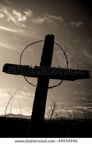 Old wooden cross from Arizona ghost town graveyard against a sepia tone clouded sky - stock photo