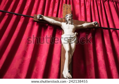 Old wooden crucifix of Jesus Christ isolated on drapery background in medieval church. - stock photo
