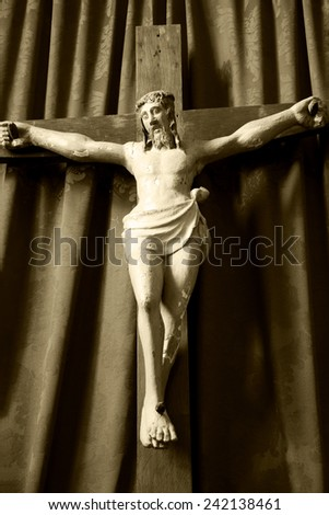 Old wooden crucifix of Jesus Christ isolated on drapery background in medieval church. Aged photo. Sepia. - stock photo